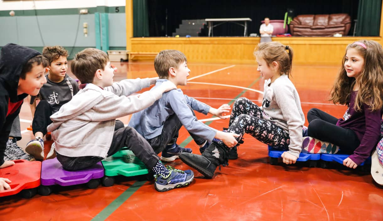 Grade 1 students roll in a line in gym