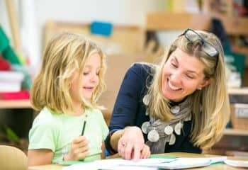 Grade 2 teacher helps young student with work