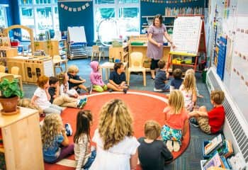 Teacher speaks to kindergarten class circle