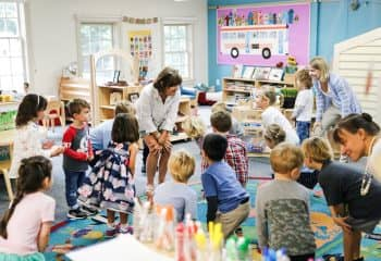 Kindergarten class gathers around teacher