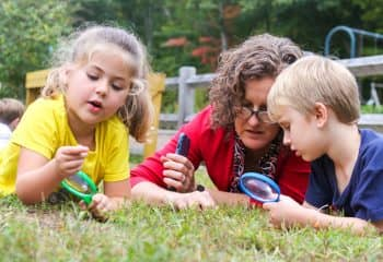 Kindergarteners and teacher look at butterflies in grass