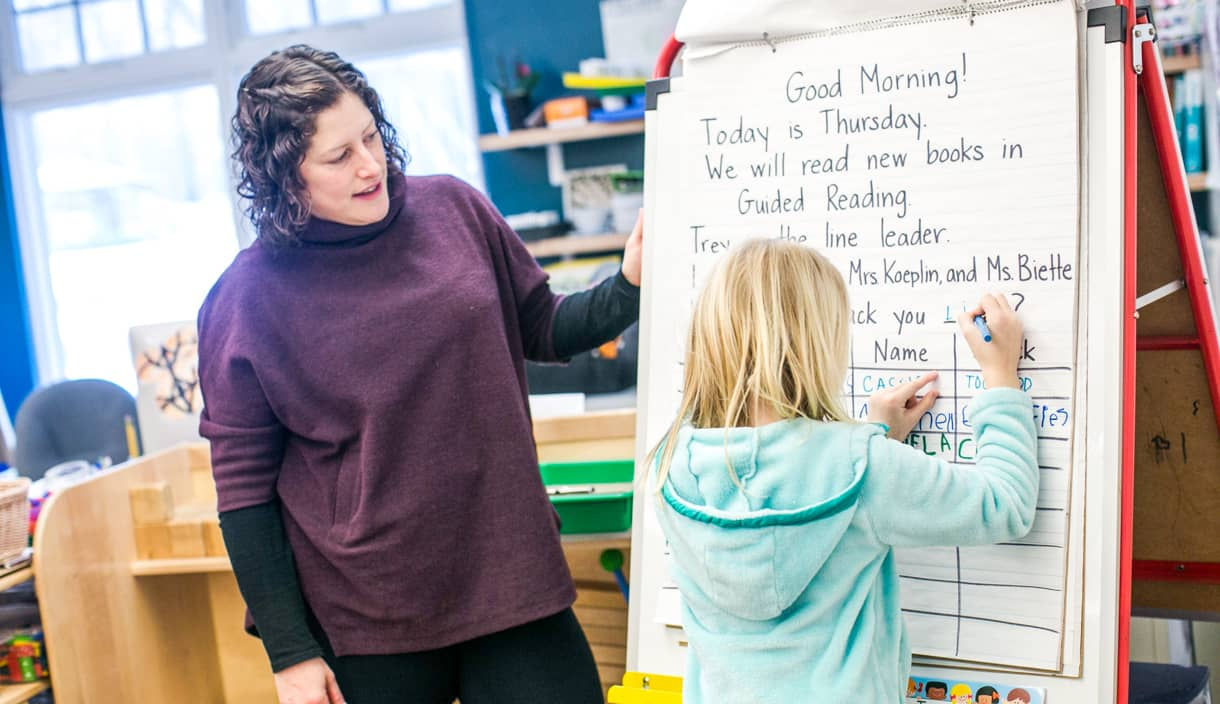 Kindergarten teacher watches as student writes on board