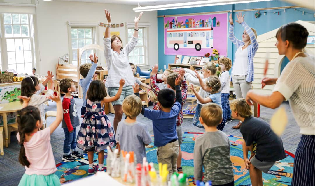 PreK class raises arms as a group