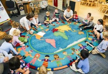 PreKindergarten class forms circle on world map rug
