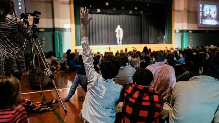 Student raises hand at school meeting