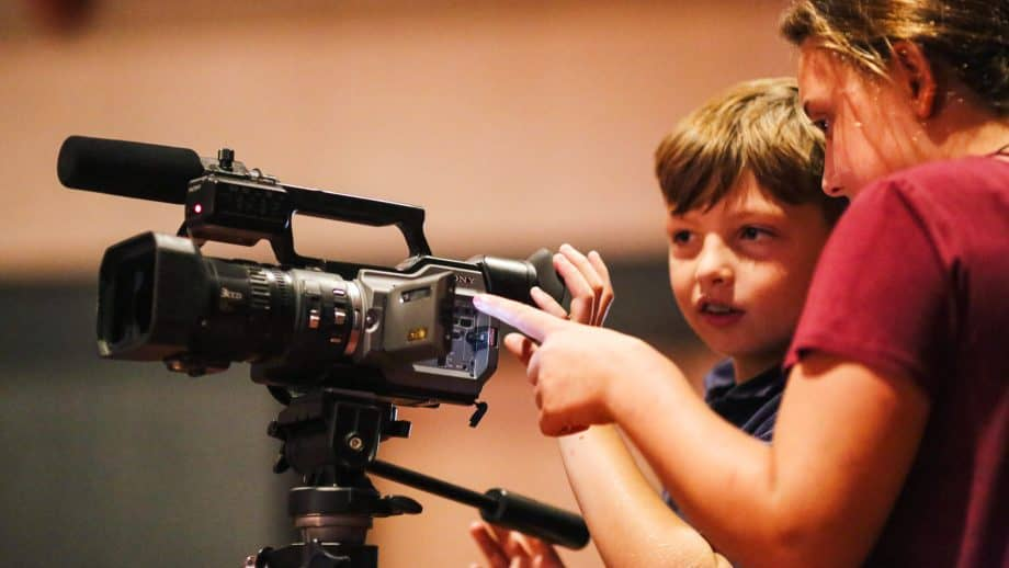 Students work video camera at school meeting