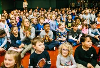 Students and teachers sit in audience of school meeting