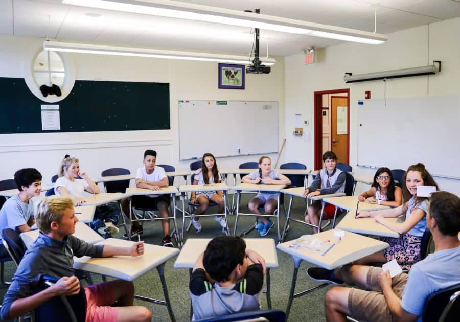 Students sit in desk circle during class