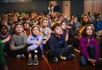 Students sit in audience during school meeting