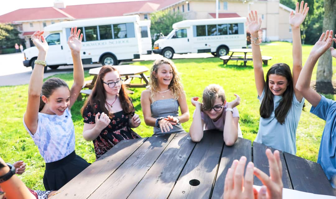 Students sitting at picnic table cheer