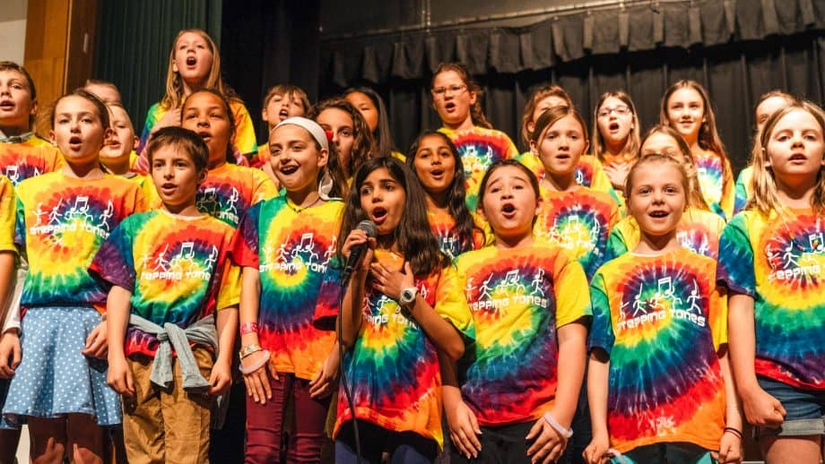 Group of students sing while wearing tie dye shirts