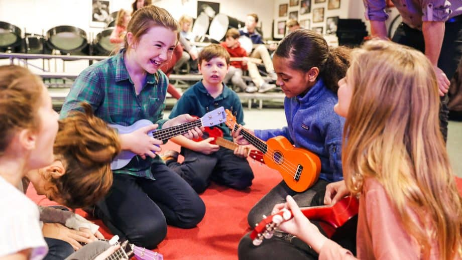 Older student leads younger students with ukeleles
