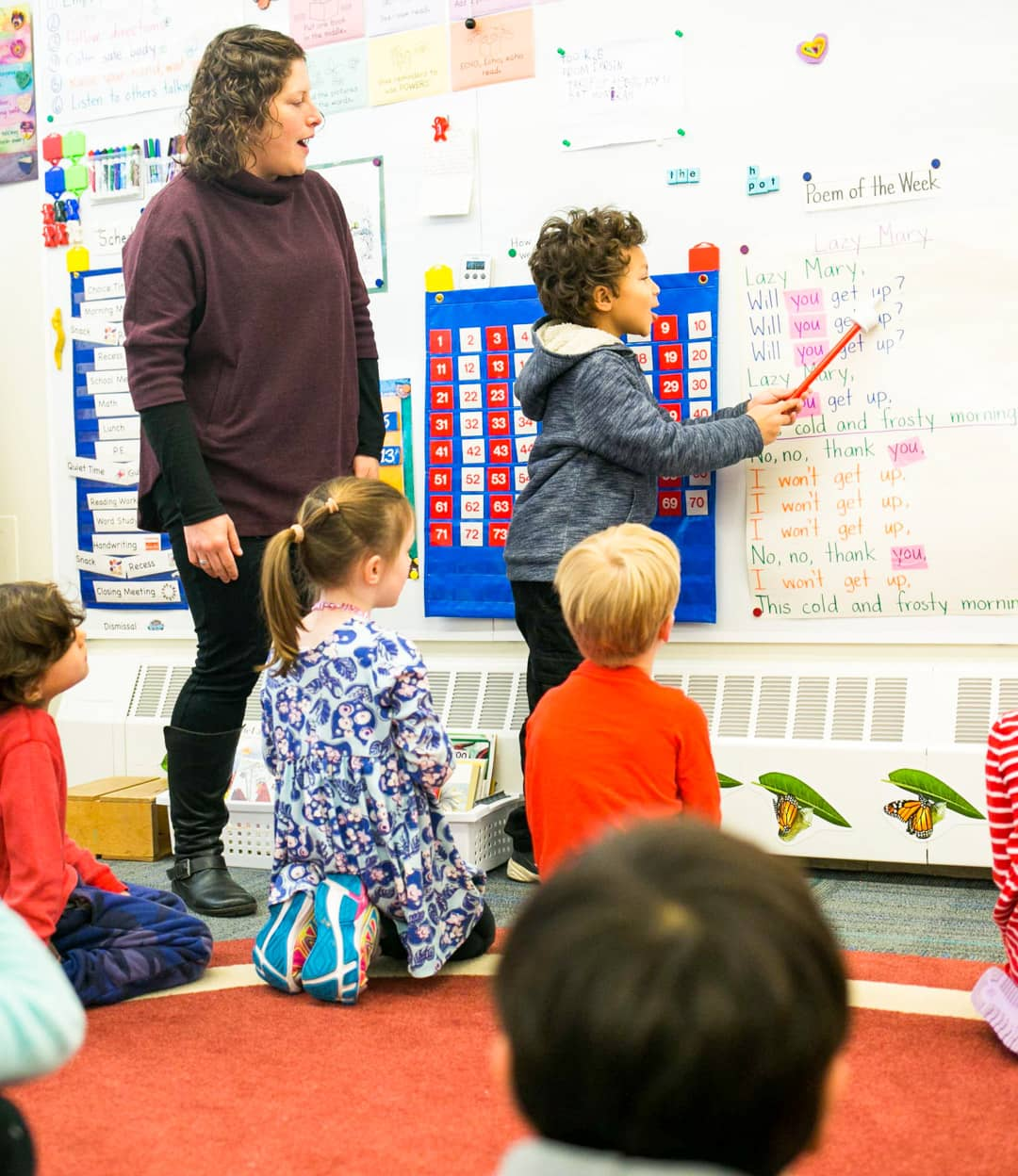 Kindergarten class watches while student points at words on wall
