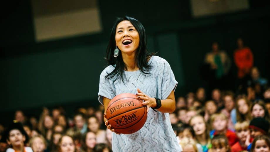 Woman holds basketball in school gym