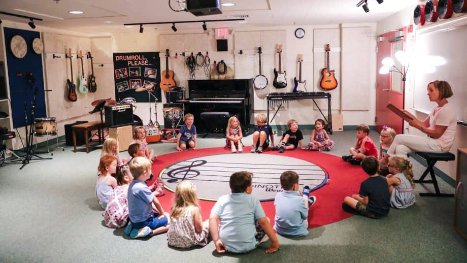 Young students gather in a circle on the music classroom floor