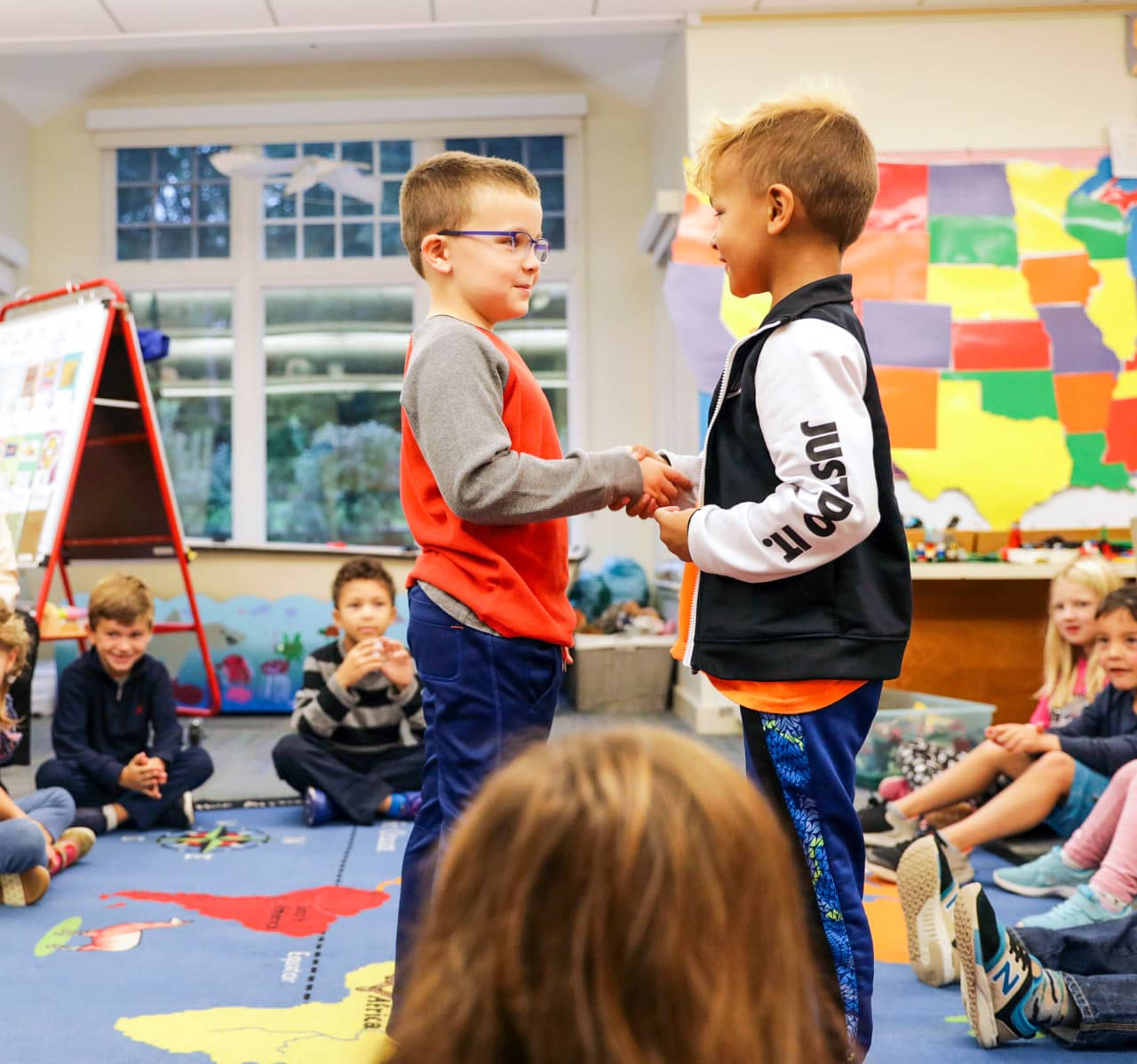 Young students shake hands in class