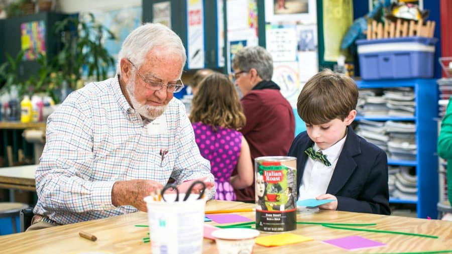 Student and older man do crafts during Grandparents' Day