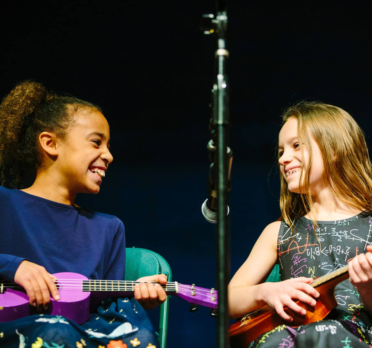 Two students play ukuleles at school meeting