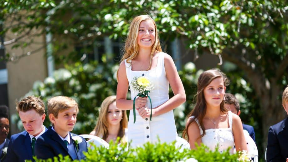 Graduating senior holds flowers and smiles
