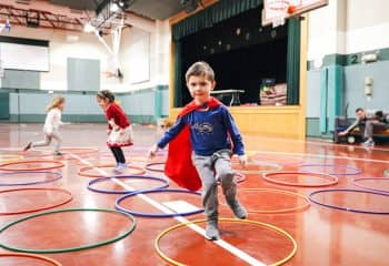 Caped student jumps across hula hoops