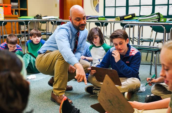 Teacher helps students sitting on the floor with clipboards